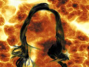 głowa kobiety bez zaznaczonej twarzy. W tle pomarańczowo-żółte płomienie