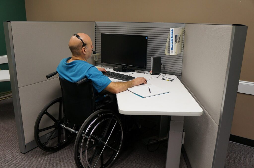 niepełnosprawny mężczyzna na wózku inwalidzkim pracujący przy komputerze. Mężczyzna ma założone słuchawki nauszne, ubrany jest w niebieski t-schirt, siedzi przy białym stoliku
