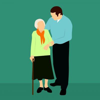 na zielonym tle starsza pani z laską przytrzymywana za rękę przez białego, ciemnowłosego mężczyznę